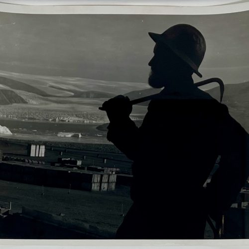 Steel worker high on a surveillance radar silhouetted against material supply area, glacier and polar icecap